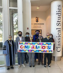 Faculty holding congrats sign